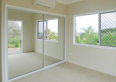 Bedroom with sliding mirror doors on cupboard